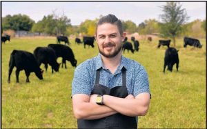 Chef Sean Sinclair stands in a field at Sol Harvest Farm, the on-site farm just outside Farm & Table restaurant in the North Valley.