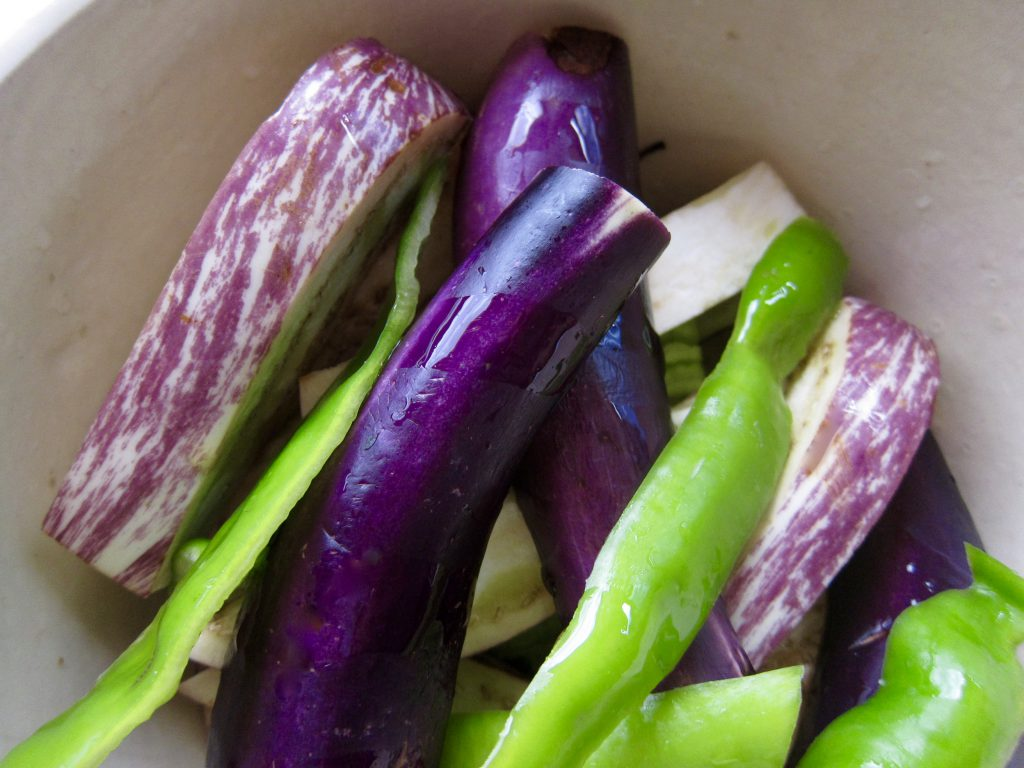 Toss green chiles and colorful eggplant with olive oil and honey.