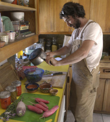 Seth Matlick, owner of Vida Verde Farms, pours caramelized butter over cooked radishes. (Greg Sorber/Albuquerque Journal)