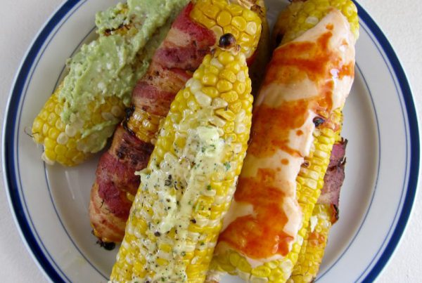 Grilled corn on the cob, served with multiple toppings, is a seasonal treat that can't be beat!
