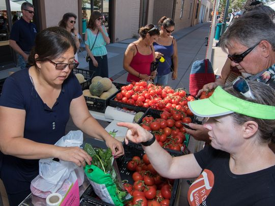 Customers purchase fresh produce at the Perfect Produce stand at the Las Cruces Farmers & Crafts Market. Local farmers as well as recipients of the food stamp incentive program benefit. (Photo: Polo Orta / For the Sun-News)