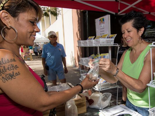 Karen Acosta-Lombino, a participant in the Double Up Food Bucks program, receives her bag of tokens from Brenda Mosely at the Las Cruces Farmers & Crafts Market. (Photo: Polo Orta / For the Sun-News)