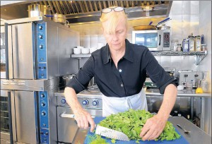 """Sarah Hartford chops broccolini in the kitchen of her restaurant, Hartford Square. Though not a fan of broccoli, Hartford likes to use broccolini. """"It has a much more complex flavor than broccoli."""""""